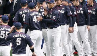 All Japan manager Atsunori Inaba, center, welcomes his players after beating MLB All-Stars 4-1 in Game 6 at their All-Stars Series baseball at Nagoya Dome in Nagoya, central Japan, Thursday, Nov. 15, 2018. Japan improved to 5-1 in the series. (Kyodo News via AP)