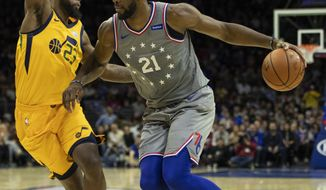 Philadelphia 76ers' Joel Embiid, right, of Cameroon, drives to the basket against Utah Jazz's Royce O'Neale, left, during the first half of an NBA basketball game, Friday, Nov. 16, 2018, in Philadelphia. (AP Photo/Chris Szagola)