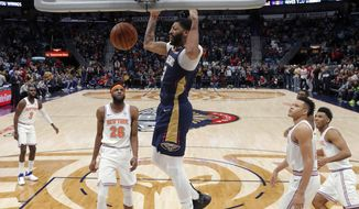New Orleans Pelicans forward Anthony Davis (23) slam dunks in front of New York Knicks center Mitchell Robinson (26) in the first half of an NBA basketball game in New Orleans, Friday, Nov. 16, 2018. (AP Photo/Gerald Herbert)