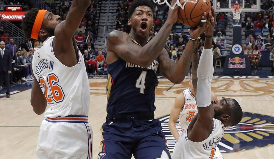 New Orleans Pelicans guard Elfrid Payton (4) goes to the basket between New York Knicks center Mitchell Robinson (26) and guard Tim Hardaway Jr. (3) in the first half of an NBA basketball game in New Orleans, Friday, Nov. 16, 2018. (AP Photo/Gerald Herbert)