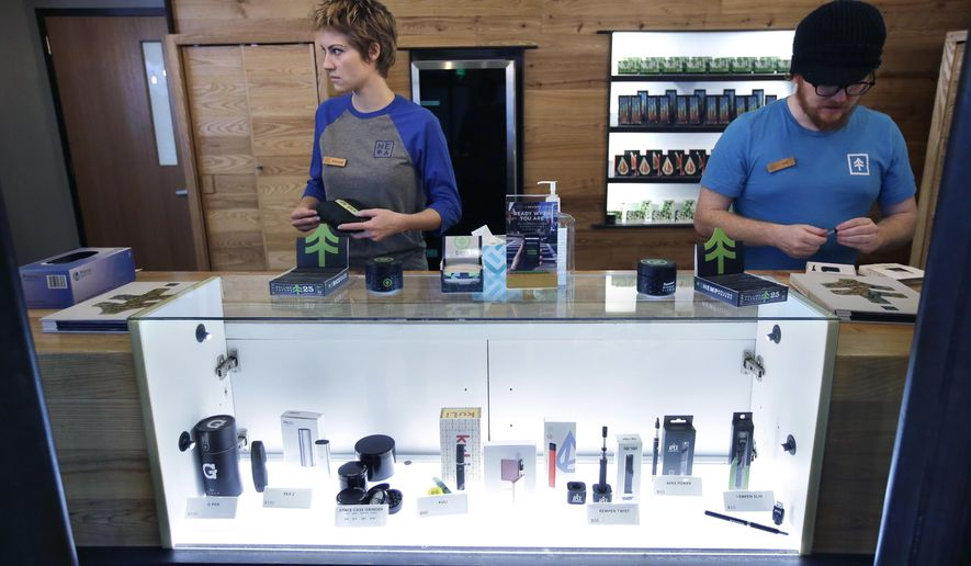 In this Wednesday, Oct. 17, 2018 photo patient service associates Savannah Stuitje, left, and Josh Hirst, right, stand at a counter that features a display of vape dispensers, below, that could be used for legal recreational cannabis, at New England Treatment Access medical marijuana dispensary, in Northampton, Mass. New England Treatment Access, and another store in Leicester, Mass., have been given the green light to begin selling recreational pot next week, making them the first commercial pot shops in the eastern United States. (AP Photo/Steven Senne, File)