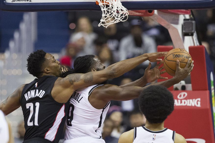 Washington Wizards center Dwight Howard (21) fouls Brooklyn Nets forward DeMarre Carroll (9) as Carroll shoots during the first half of an NBA basketball game Friday, Nov. 16, 2018, in Washington. (AP Photo/Alex Brandon)
