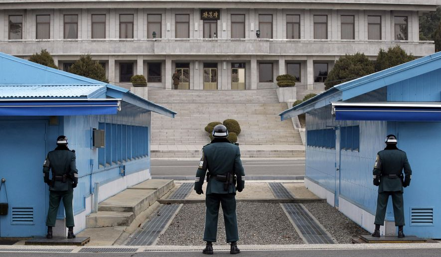 In this March 12, 2014, file photo, a North Korean soldier, center top, looks at the southern side as three South Korean soldiers guard at the border village of Panmunjom, which has separated the two Koreas since the Korean War, in Paju, South Korea. (AP Photo/Lee Jin-man, File) **FILE**