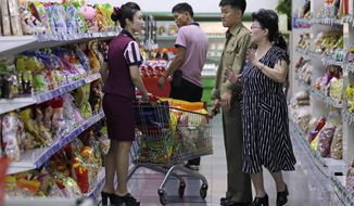 FILE - In this Sept. 12, 2018, file photo, North Korean customers get assistance at a supermarket in Pyongyang, North Korea. One of the biggest mysteries among North Korea economy watchers is how the country has managed to maintain stable exchange rates despite intense sanctions, political tensions and a swelling trade imbalance. The North claims it simply shows how strong the economy really is. But outside experts say it could reflect anything from tight loan policies and government restrictions on speculative dealing to a massive sell-off of state assets. (AP Photo/Kin Cheung, File)