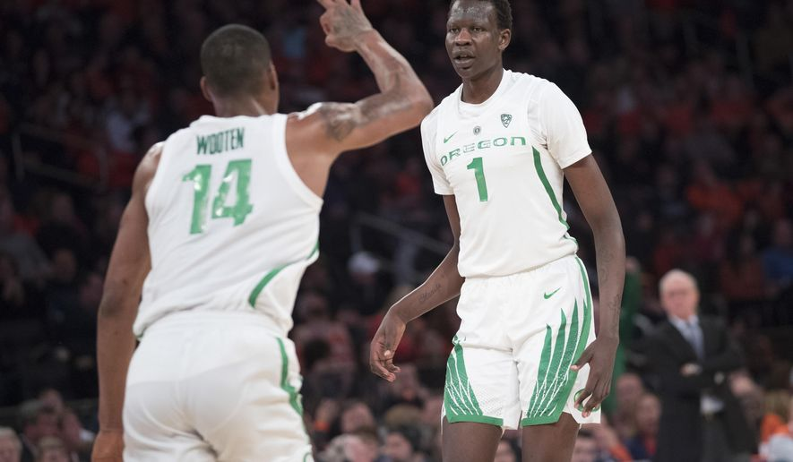 Oregon forward Kenny Wooten (14) and center Bol Bol (1) react after Bol Bol scored a three-point goal during the second half of an NCAA college basketball consolation game against Syracuse in the 2K Empire Classic, Friday, Nov. 16, 2018, at Madison Square Garden in New York. (AP Photo/Mary Altaffer)