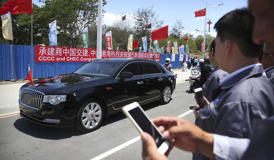 A limousine carrying Chinese President Xi Jinping travels in a motorcade along the newly-dedicated Independence Drive Boulevard in Port Moresby, Papua New Guinea, Friday, Nov. 16, 2018. (AP Photo/Mark Schiefelbein, Pool)