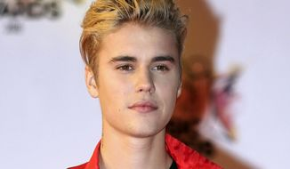 FILE - In this Nov. 7, 2015 file photo, Justin Bieber arrives at the Cannes festival palace in Cannes, southeastern France. Bieber and a former neighbor whose house he egged have agreed to a settlement in a long-running lawsuit. A document filed Friday, Nov. 16, 2018, shows the case has been resolved in its entirety. No details were given about the terms. (AP Photo/Lionel Cironneau, File)