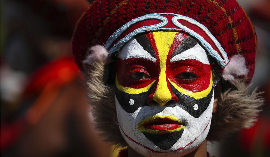 A performer in traditional clothing and makeup waits for the start of a welcome ceremony for Chinese President Xi Jinping in Port Moresby, Papua New Guinea, Friday, Nov. 16, 2018. The largely undeveloped South Pacific nation of more than 8 million mostly subsistence farmers hopes the rare world attention generated by its hosting of the Asia Pacific Economic Economic Cooperation meetings will highlight its potential and draw more investors and aid. (AP Photo/Mark Schiefelbein)