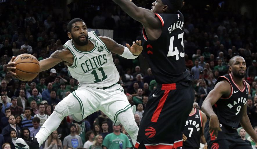 Boston Celtics guard Kyrie Irving (11) passes the ball against the defense of Toronto Raptors forwards Pascal Siakam (43) and Serge Ibaka (9) in the fourth quarter of an NBA basketball game, Friday, Nov. 16, 2018, in Boston. Irving scored 43 points to lead the Celtics to a 123-116 victory in overtime. (AP Photo/Elise Amendola)
