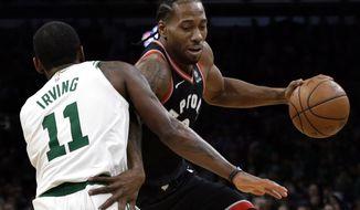 Toronto Raptors forward Kawhi Leonard drives around Boston Celtics guard Kyrie Irving (11) in the first quarter of an NBA basketball game, Friday, Nov. 16, 2018, in Boston. (AP Photo/Elise Amendola)