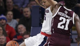 Gonzaga forward Brandon Clarke, left, dunks while defended by Texas A&M forward Christian Mekowulu (21) during the first half of an NCAA college basketball game in Spokane, Wash., Thursday, Nov. 15, 2018. (AP Photo/Young Kwak)