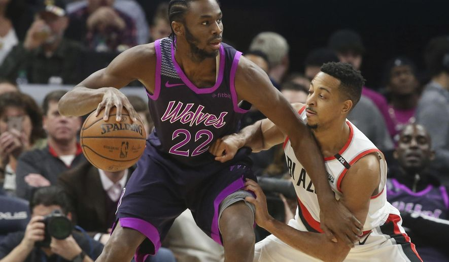 Minnesota Timberwolves' Andrew Wiggins, left, drives against Portland Trail Blazers' CJ McCollum during the first half of an NBA basketball game Friday, Nov. 16, 2018, in Minneapolis. The Timberwolves players paid tribute to the musician Prince, who died in 2016, with new purple-trimmed uniforms. (AP Photo/Jim Mone)