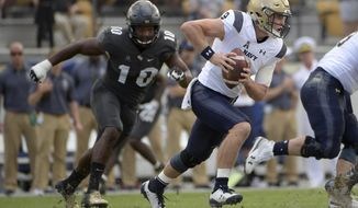 FILE - In this Nov. 10, 2018, file photo, Navy quarterback Zach Abey (9) rushes for yardage in front of Central Florida defensive lineman Titus Davis (10) during the first half of an NCAA college football game in Orlando, Fla. Navy faces Tulsa on Saturday. (AP Photo/Phelan M. Ebenhack) ** FILE **