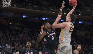 Iowa forward Luka Garza (55) shoots over Connecticut forward Eric Cobb (0) during the first half of an NCAA college basketball final game in the 2K Empire Classic, Friday, Nov. 16, 2018, at Madison Square Garden in New York. (AP Photo/Mary Altaffer)