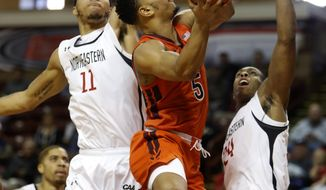 Virginia Tech's Justin Robinson, center, drives between Northeastern's Jeremy Miller, at left, and Shaquille Walters in the first half of an NCAA college basketball game at the Charleston Classic at TD Arena, Friday, Nov. 16, 2018, in Charleston, S.C. Virginia Tech defeated Northeastern 88-60. (AP Photo/Mic Smith)
