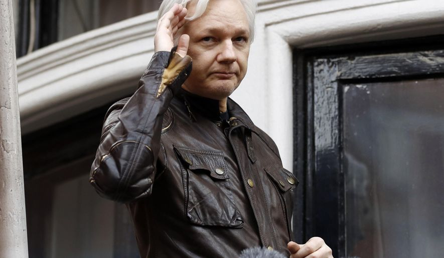 FILE - In this May 19, 2017, file photo, WikiLeaks founder Julian Assange greets supporters from a balcony of the Ecuadorian embassy in London. The Justice Department inadvertently named Assange in a court filing in an unrelated case that raised immediate questions about whether the WikiLeaks founder had been charged under seal. Assange's name appears twice in an August 2018 filing from a prosecutor in Virginia in a separate case involving a man accused of coercing a minor. (AP Photo/Frank Augstein, File)