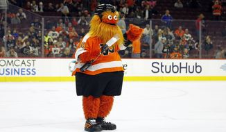 FILE - In this Sept. 24, 2018 file photo, the Philadelphia Flyers mascot, Gritty, takes to the ice during the first intermission of the Flyers' preseason NHL hockey game against the Boston Bruins in Philadelphia. In video shared on his Twitter account, Gritty proclaimed his love for snow on Thursday, Nov. 15,  by shuffling his feet to form the shape of a heart. The 7-foot (2-meter) furry, orange creature was introduced in September.  (AP Photo/Tom Mihalek, File)
