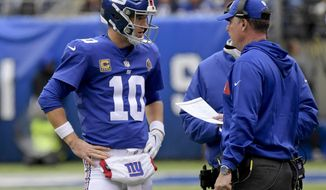 FILE - In this Oct. 28, 2018, file photo, New York Giants quarterback Eli Manning (10) talks with head coach Pat Shurmur during the second quarter of an NFL football game in East Rutherford, N.J. When things go sour, an NFL team's fan base often points to two people: the guy calling plays on the sideline, and the man behind center trying to execute them. (AP Photo/Bill Kostroun, File)