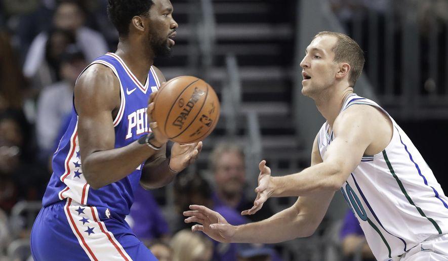 Philadelphia 76ers' Joel Embiid, left, drives against Charlotte Hornets's Cody Zeller during the first half of an NBA basketball game in Charlotte, N.C., Saturday, Nov. 17, 2018. (AP Photo/Chuck Burton)