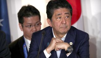 Japan's Prime Minister Shinzo Abe attends a signing ceremony for the Papua New Guinea Electrification Partnership at APEC Haus in Port Moresby, Papua New Guinea, Sunday, Nov. 18, 2018. (AP Photo/Mark Schiefelbein)
