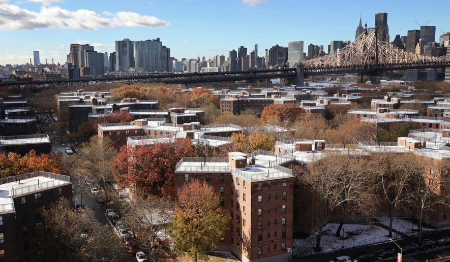 The Queensbridge Houses sit beneath the Ed Koch Queensboro Bridge, upper right, Friday, Nov. 16, 2018, in New York. Like most New York City housing projects, Queensbridge residents complain of poor conditions, lacking heat or hot water, or rats and roaches. The city has come under sharp criticism for the conditions of its public housing. Amazon is proposing to build a new headquarters nearby. (AP Photo/Mark Lennihan)