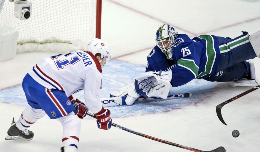 Montreal Canadiens' Brendan Gallagher, left, reaches for the puck in front of Vancouver Canucks goalie Jacob Markstrom, of Sweden, during the second period of an NHL hockey game in Vancouver, British Columbia, Saturday, Nov. 17, 2018. (Darryl Dyck/The Canadian Press via AP)
