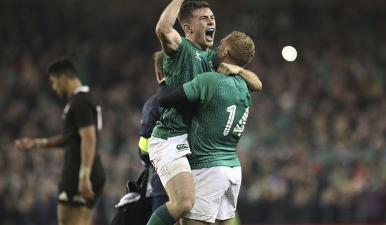 Ireland's Luke McGrath, left, celebrates with Ireland's Keith Earls after the rugby union international between Ireland and the New Zealand All Blacks in Dublin, Ireland, Saturday, Nov. 17, 2018. Ireland won the match 16-9. (AP Photo/Peter Morrison)