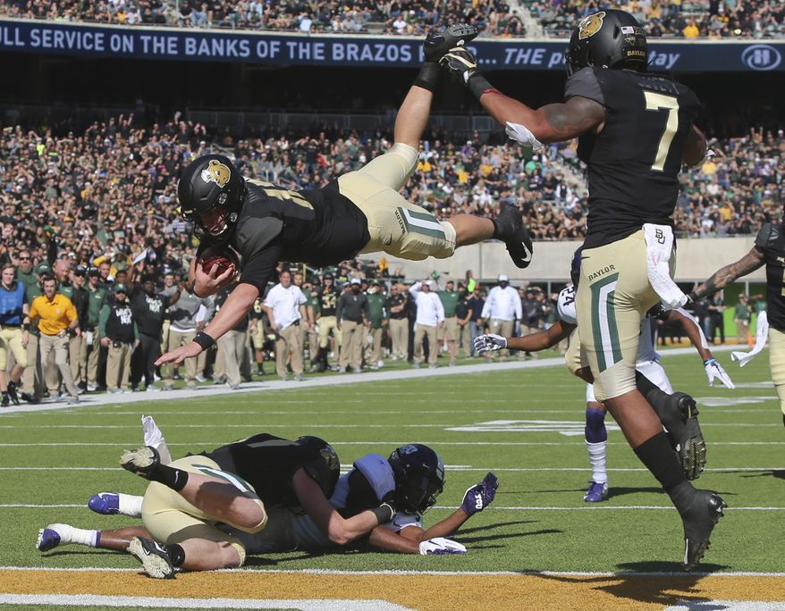 Baylor quarterback Charlie Brewer, center, dives over the goal line for a touchdown in the first half of an NCAA college football game against TCU, Saturday, Nov. 17, 2018, in Waco, Texas. (Michael Bancale/Waco Tribune Herald, via AP)