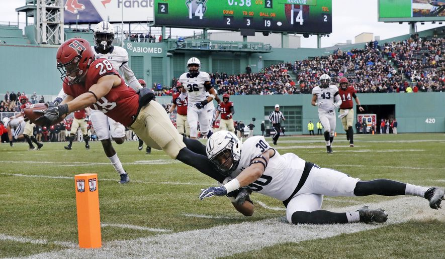 Harvard wide receiver Henry Taylor (28) stretches for a touchdown against Yale linebacker Noah Pope (30) during the first half of an NCAA college football game at Fenway Park in Boston, Saturday, Nov. 17, 2018. (AP Photo/Charles Krupa)