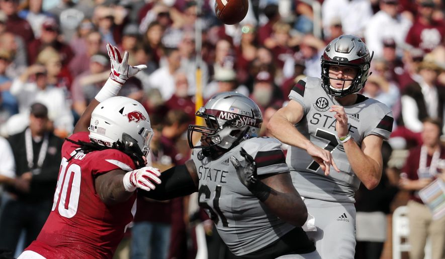 Mississippi State quarterback Nick Fitzgerald (7) passes against an on rushing Arkansas defender during the first half of an NCAA college football game in Starkville, Miss., Saturday, Nov. 17, 2018. (AP Photo/Rogelio V. Solis)