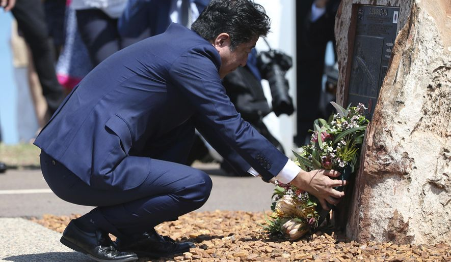 Japan's Prime Minister Shinzo Abe places flowers at a memorial of the 80-crew Japanese submarine I-124, which was sunk off Darwin in January 1942, in Darwin, Australia Saturday, Nov. 17, 2018 (David Moir/Pool Photo via AP)