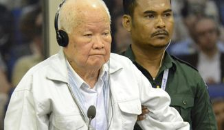 In this photo released by the Extraordinary Chambers in the Courts of Cambodia, Khieu Samphan, foreground, former Khmer Rouge head of state, stands at thea dock in a court room during a hearing at the U.N.-backed war crimes tribunal in Phnom Penh, Cambodia, Friday, Nov. 16, 2018. A U.N.-backed tribunal in Cambodia on Friday convicted the two most senior surviving leaders of the country's former Khmer Rouge regime of genocide and other crimes against humanity, sentencing them to life in prison. (Nhet Sok Heng/Extraordinary Chambers in the Courts of Cambodia via AP)