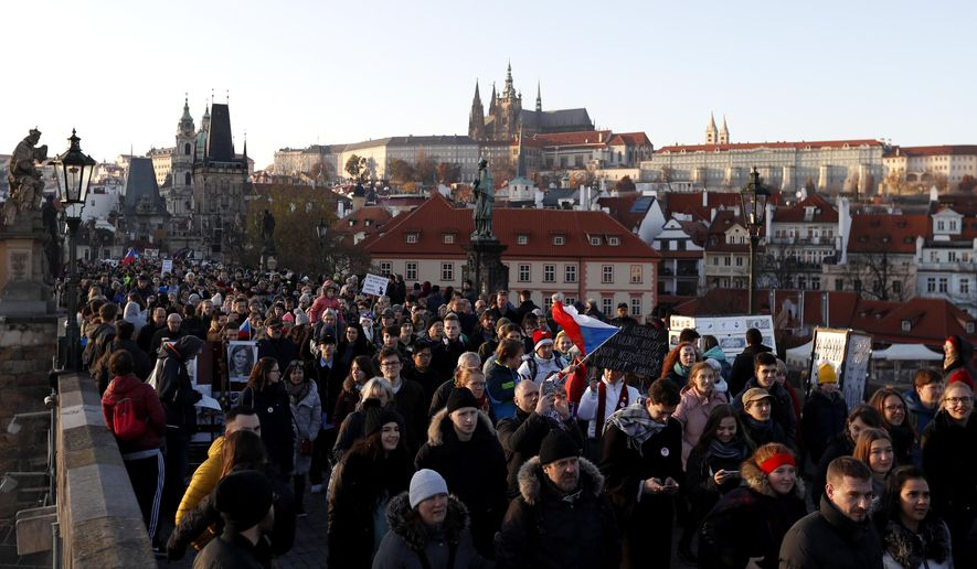 Thousands of Czechs, using the 29th anniversary of the anti-communist Velvet Revolution, gather for march to call on the Czech Republic's Prime Minister Andrej Babis to resign in Prague, Czech Republic, Saturday, Nov. 17, 2018. Babis faces allegations that he has misused EU subsidies for a farm he transferred to his family members, though he denies wrongdoing. The Prague Castle is in the background. (AP Photo/Petr David Josek)