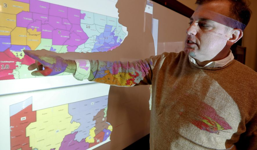 "William Marx, points to projected images of the old congressional districts of Pennsylvania on top, and the new re-drawn districts on the bottom, while standing in the classroom where he teaches civics in Pittsburgh on Friday, Nov. 16, 2018. Marx was a plaintiff in the Pennsylvania lawsuit that successfully challenged the Republican-drawn congressional maps. Marx said he believes the new district boundaries resulted in ""a more fair congressional representation of the will of the people in Pennsylvania."" (AP Photo/Keith Srakocic)"