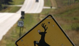In this Oct. 8, 2007 photo, a deer crossing sign looks south on Highway 50 in Nebraska City, Neb. (Kent Sievers/Omaha World-Herald via AP)