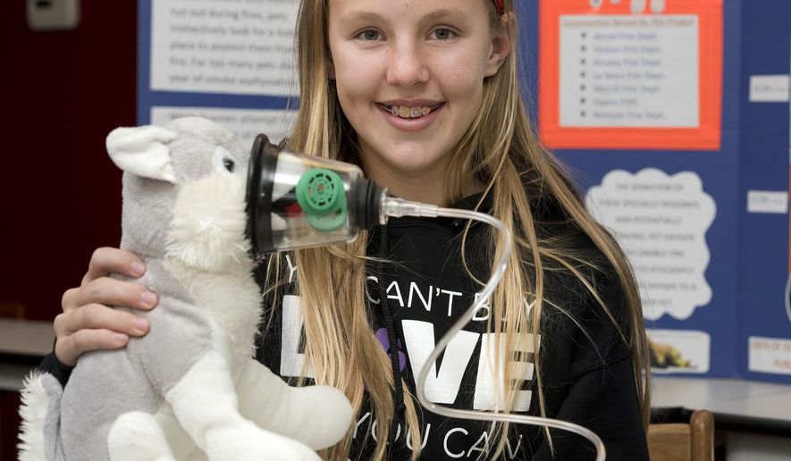 Brooklyn Bockelmann, a eighth-grader at Le Mars Middle School, demonstrates how a pet oxygen mask is used during an interview Thursday, Nov. 1, 2018, at the Le Mars Fire Department in Le Mars, Iowa. Bockelmann has been raising money to purchase sets of pet oxygen masks to donate them to area fire departments. She has the goal of raising money to donate a set of the masts to every fire department in Iowa that wants one. (Tim Hynds/Sioux City Journal via AP)