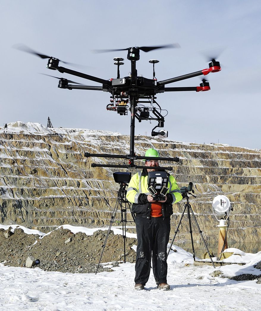 In this Nov. 9, 2018, photo, Ian Fairweather, of Montana Resources, operates a drone that is specially designed to haze waterfowl that land on the Berkeley Pit, a former open pit copper mine in Butte, Mont. Montana Resources uses boats, drones, rifles and sometimes fireworks to keep birds off of water in the pit, filled with water that is heavily acidic. (Meagan Thompson/Montana Standard via AP)