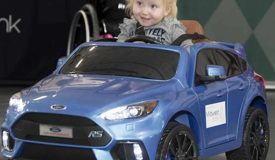 In this Friday, Nov. 2, 2018 photo, Reagan Graham, 2, rides in her new electric toy vehicle, with adaptations designed to accommodate her disability at Rolling Hills Trading, in Lincoln, Neb. The nonprofit Seeking More Independent Life Experiences (S.M.I.L.E.) and Madonna Research Institute collaborated to present adapted vehicles to three patients of Madonna's pediatric outpatient therapy. (Gwyneth Roberts/Lincoln Journal Star via AP)