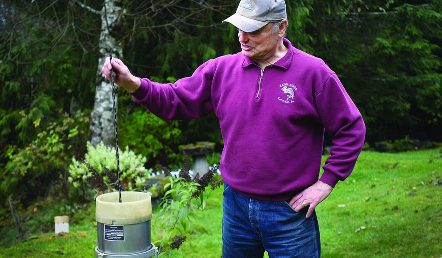 This Nov. 2, 2018, photo shows Bill Hopkins taking a reading from a rain meter at his home in Ketchikan, Alaska. Hopkin and his wife, Wynn, have been recording weather measures for the National Weather Service since 2001. (Dustin Safranek/Ketchikan Daily News via AP)