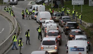 Demonstrators block a motorway exit to protest fuel tax, in Marseille, southern France, Tuesday, Nov. 17, 2018. France is bracing for a nationwide traffic mess as drivers plan to block roads to protest rising fuel taxes, in a new challenge to embattled President Emmanuel Macron. (AP Photo/Claude Paris)