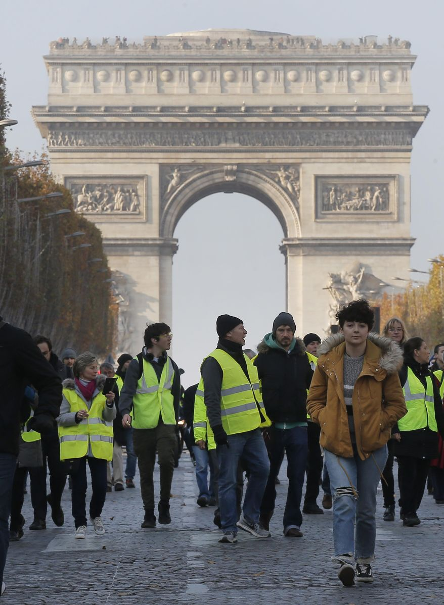 Protesters walk on the Champs Elysees avenue to protest fuel taxes in Paris, France, Saturday, Nov. 17, 2018. France is bracing for a nationwide traffic mess as drivers plan to block roads to protest rising fuel taxes, in a new challenge to embattled President Emmanuel Macron. (AP Photo/Michel Euler)