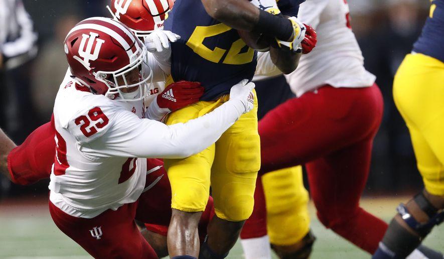 Michigan running back Karan Higdon (22) runs as Indiana defensive back Khalil Bryant (29) makes the tackle in the first half of an NCAA college football game in Ann Arbor, Mich., Saturday, Nov. 17, 2018. (AP Photo/Paul Sancya)
