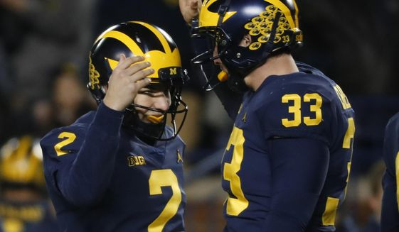 Michigan place kicker Jake Moody (2) celebrates kicking a 29-yard field goal with long snapper Camaron Cheeseman (33) in the second half of an NCAA college football game against Indiana in Ann Arbor, Mich., Saturday, Nov. 17, 2018. Michigan won 31-20. (AP Photo/Paul Sancya) ** FILE **