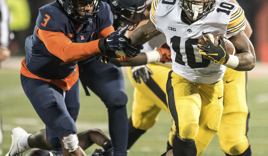 Iowa's Mekhi Sargent (10) breaks the tackle of Illinois 'Del'Shawn Phillips (3) in the second half of a NCAA college football game, Saturday, Nov. 17, 2018, in Champaign, Ill. (AP Photo/Holly Hart)