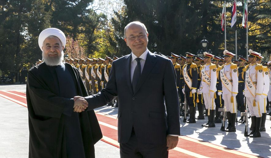 In this photo released by official website of the Office of the Iranian Presidency, Iraqi President Barham Salih, right, and his Iranian counterpart Hassan Rouhani shake hands during an official welcome ceremony for Salih at the Saadabad Palace in Tehran, Iran, Saturday, Nov. 17, 2018. Salih is visiting Iran less than two weeks after the United States restored oil sanctions that had been lifted under the 2015 nuclear deal. (Iranian Presidency Office via AP)