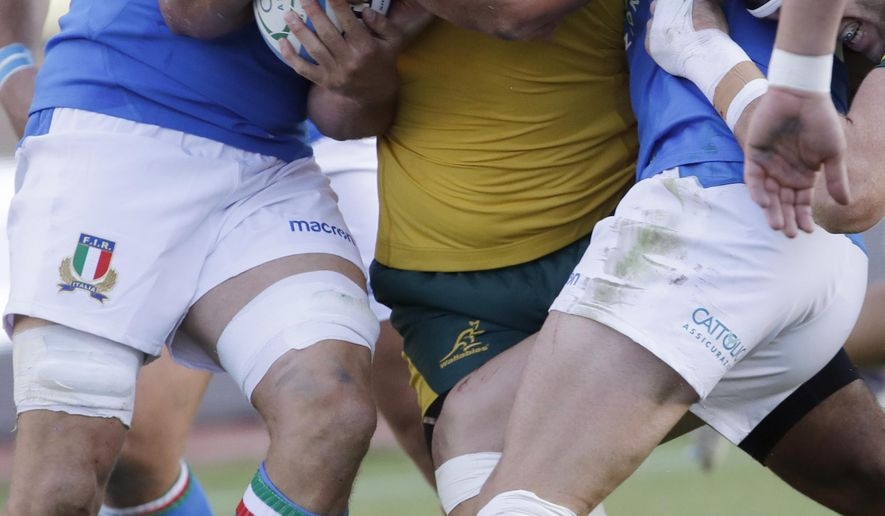 Australia's Scott Sio, center, is tackled by Italian players during the rugby union international match between Italy and Australia at the Euganeo Stadium in Padua, Italy, Saturday, Nov. 17, 2018. (AP Photo/Luca Bruno)