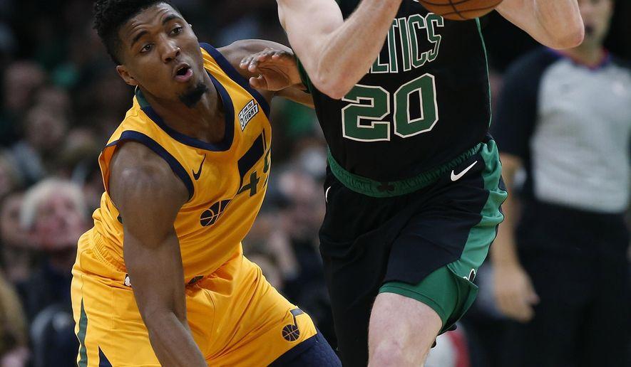 Boston Celtics' Gordon Hayward (20) and Utah Jazz's Donovan Mitchell (45) battle for the  e ball during the first half on an NBA basketball game in Boston, Saturday, Nov. 17, 2018. (AP Photo/Michael Dwyer)