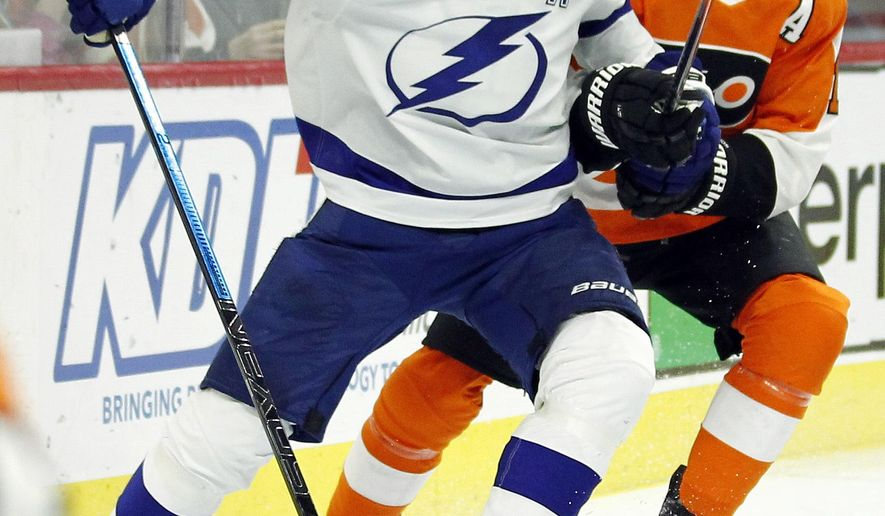 Tampa Bay Lightning' Victor Hedman, left, holds on to the stick of Philadelphia Flyers' Wayne Simmonds during the second period of an NHL hockey game, Saturday, Nov. 17, 2018, in Philadelphia. Hedman got a two-minute penalty. (AP Photo/Tom Mihalek)