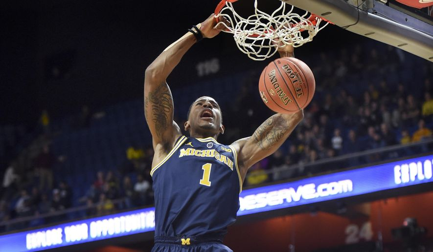 Michigan's Charles Matthews (1) dunks in the first half of an NCAA college basketball game against George Washington Saturday, Nov. 17, 2018, in Uncasville, Conn. (AP Photo/Stephen Dunn)