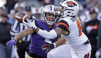 Oregon State's Trevon Bradford, right, catches the ball in front of Washington's Myles Bryant in the first half of an NCAA college football game Saturday, Nov. 17, 2018, in Seattle. (AP Photo/Elaine Thompson)